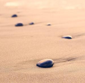 Immagine distensiva di sassi neri su sabbia nel deserto